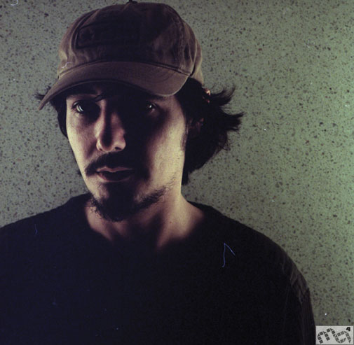 Amon Tobin with beard, hat, expansive hair.